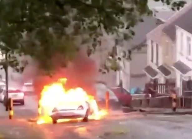 Moment burning car flies down street as vigil for dead teenager turns into riot